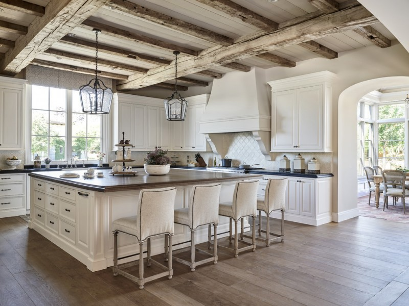 summer kitchen with wooden flooring, wooden beam ceiling, arch walls, white kitchen islands with brown top, white counter with black top, white big cooker hood