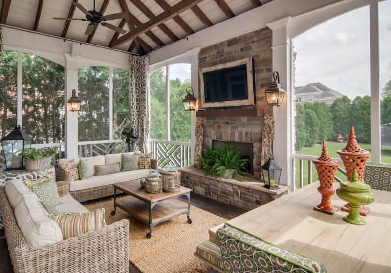 sunroom in porch with grey rattan sofas with white cushions, wooden coffee table, TV on tile wainscoting wall, ceiling fan, sconces, windows around