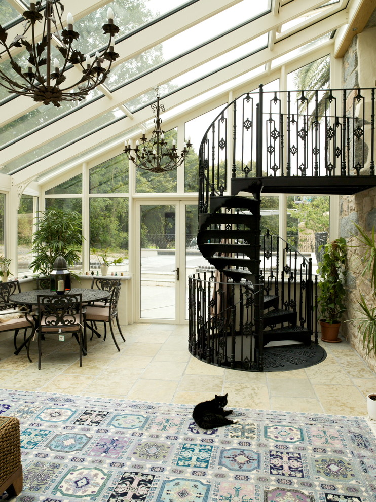 sunroom with angled ceiling from glass, glass wall, with blue rug, black metal chairs with black wooden table, black wrought iron chandelier, black metal stair