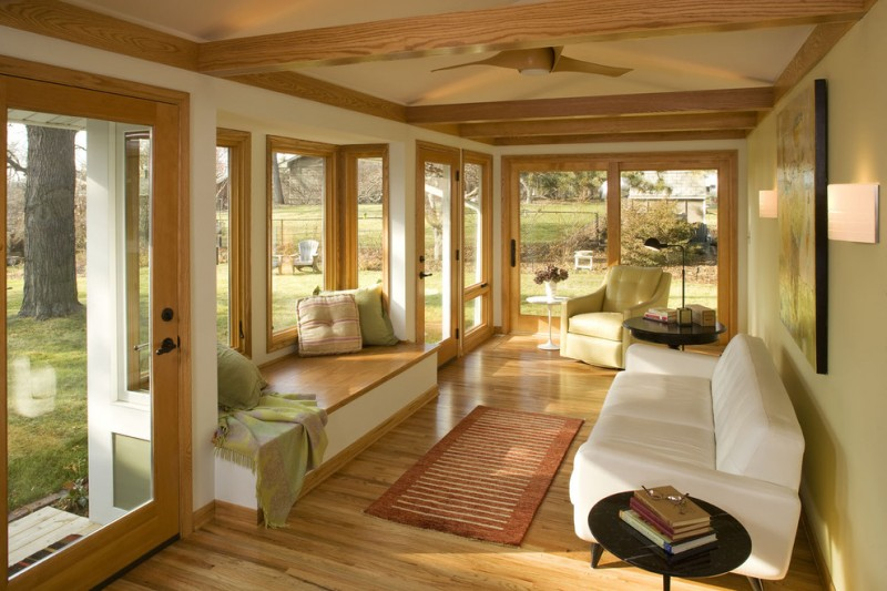 sunroom with brown wood flooring, brown wood framed glass windows and doors, wooden build in sofa, white sofa, beige chair, white ceiling with wood beams
