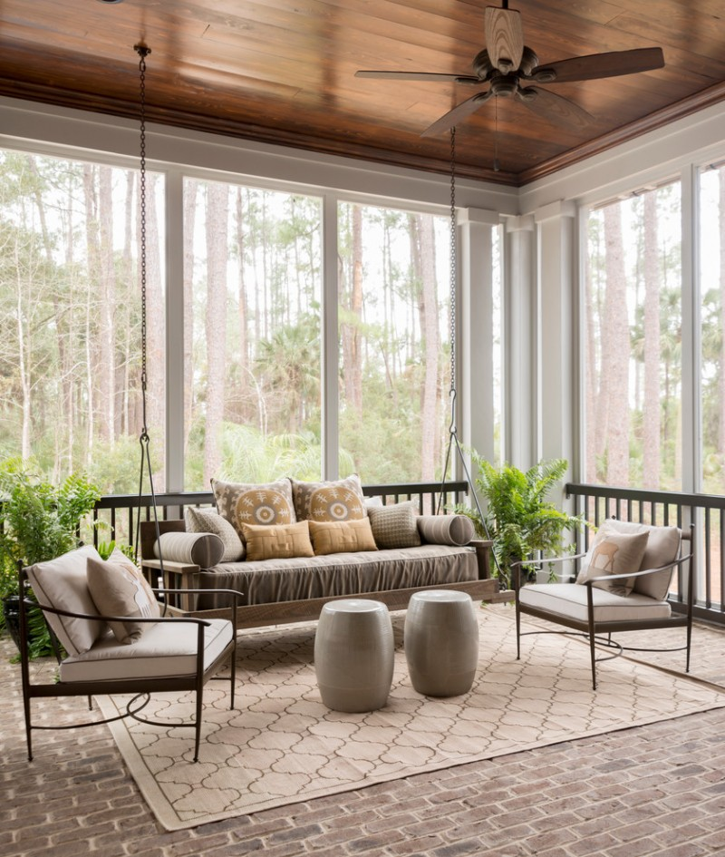 sunroom with grey flooring, big windows around with white see trough curtain, wooden swing sofa withbrown cushions, metal chair with cushion, rugs, round ottoman for table, ceiling fan