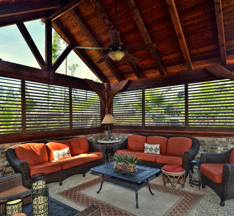 sunroom with stone floow, wooden vaulted ceiling, wooden rail windows, black rattan sofa with red cushion, blak coffee table, side table, table lamp, red ottoman