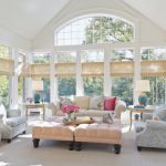 Sunroom With White Vaulted Ceiling, Windows Around, Blue Sofas, Soft Orange Ottoman For Table, Soft Yellow Sofa, Pillows, Rattan Curtain, Rattan Round Ottoman, Side Tables, Table Lamps