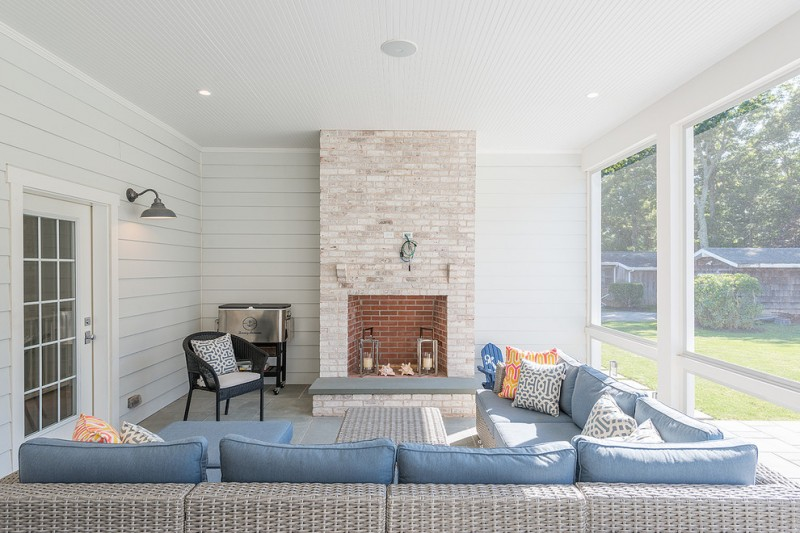 sunroom with white wall, grey rattan corner sofa with blue cushions, black rattan chair, big window in one side, decorated with fire place in orange stone