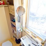 Tiny Bahtroom With White Small Square Sink, Retractble Mirror, Big Glass Window, Brown Wooden Shelves On The Right
