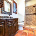 Topcoat Of Granite Vanity And Dark Wood Cabinets Mirror With Art Frames Yellow Orange Tiles Floors Terracotta Floors And Walls In Shower Space White Toilet