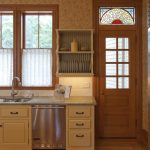 Traditional Kitchen Design With Mediterranean Touch White Cafe Curtains Marble Countertop White Cabinetry White Subway Tile Backsplash Walls With Traditional Wallpaper Door With Art Glass Panel On Top