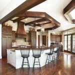 Traditional Kitchen With Dark Floor, White Island With Dark Wood Counter Top, Dark Wood Cabinet, White Ceiling With Wood Beam