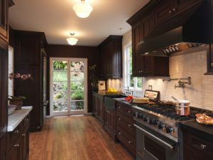 traditional kitchen with wood floor, dark wood cabinet, soft light brown backsplash