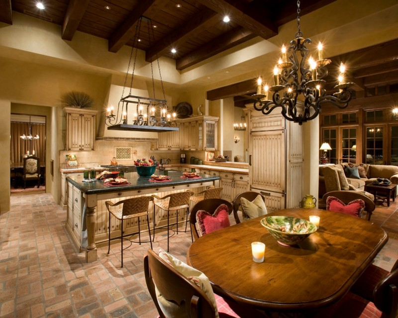 traditional mediterranean dining room with sand color stone floor, wooden beams ceiling, wooden table and chair with colorful pillows, white wall