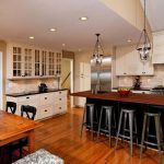 Traditional Open Kitchen With Wooden Flooring, White Cabinet, Black Counter, Wooden Counter Top, Wooden Dining Table, Pendant Lights, Beige Tiles Wall