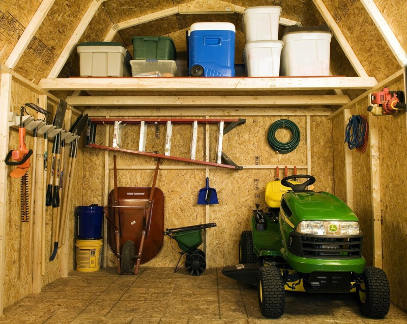 traditional shed interior made of plywood a lot of gardening tools and big storage boxes