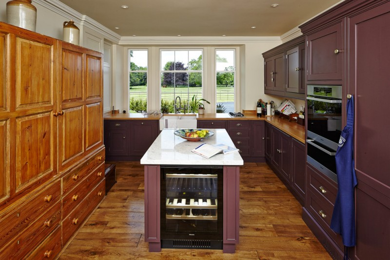 transitional L shape kitchen idea with wood countertop deep purple cabinets deep purple kitchen island with white top wooden floors with clear finishing white farmhouse sink stainless steel appliances