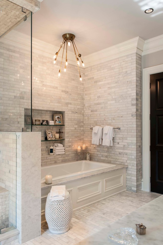 transitional bathroom with white drop in tub white marble countertop light grey subway tiles floors and walls modern ceiling lamps decorative side table in white