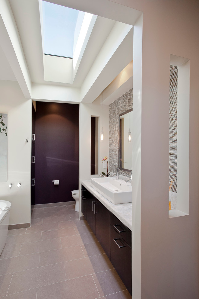 trendy bathroom with modern vanity unique and textured vanity walls trough vessel in white flat panel cabinets light beige tiles floors white bathtub white toilet