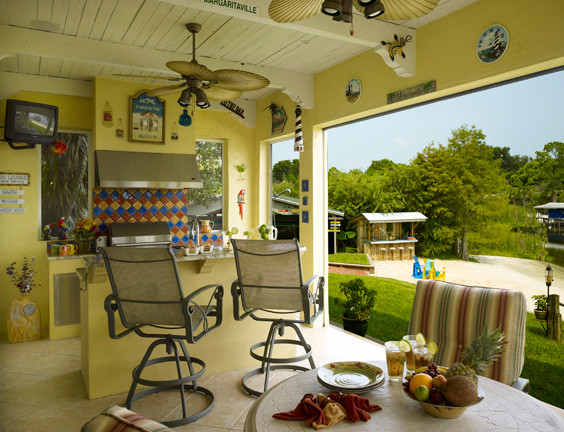 tropical summer kitchen with yellow wall, ceilig fans, colorful tiles and colorful chair