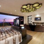 tv display decoration contemporary bedroom wood floor shelves sofa pillows railing ceiling lamp