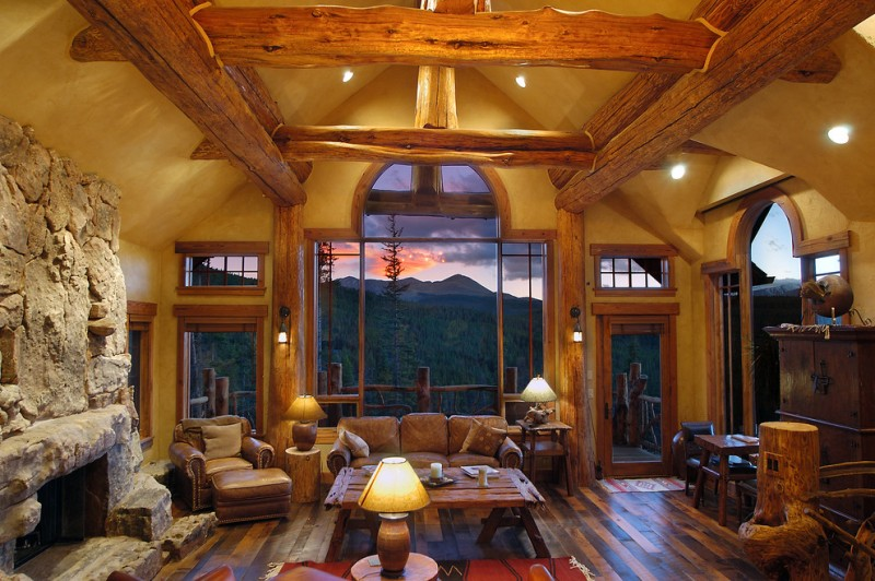 two floor stone and log house stone fireplace table sofa pillows door windows lamps wood floor logs
