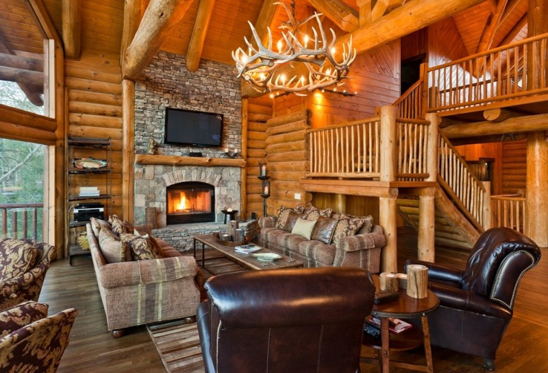 two floor stone and log house wood floor carpet stairs chandelier sofa pillows fireplace logs glass wall tv