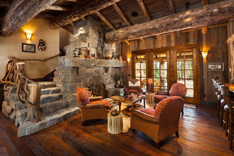 two floor stone and log house wood floor stone staircase logs wall lamp lighting sofas table door chairs