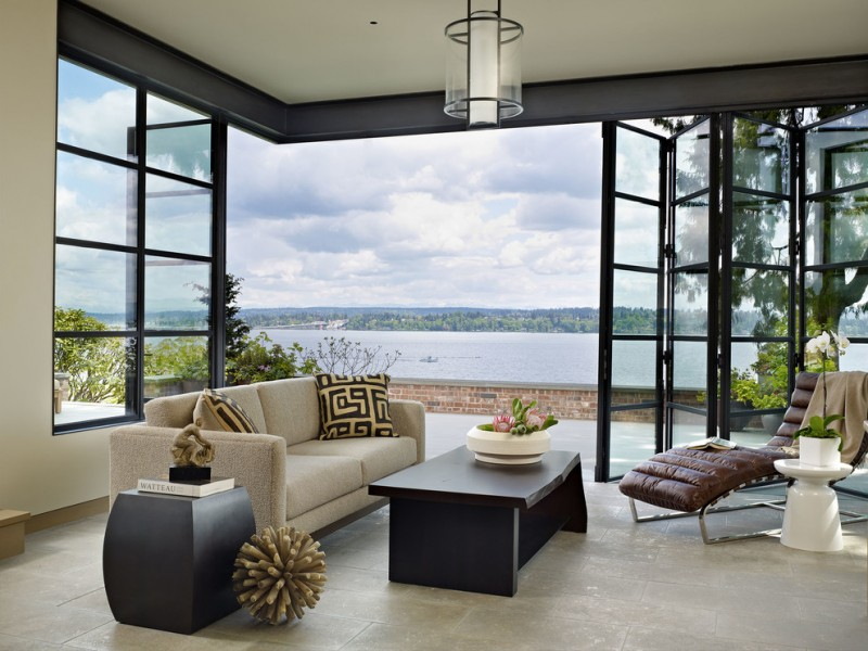 unique steel doors sofa pillows window floor to ceiling steel and glass door hanging lamp pot flowers bricks table