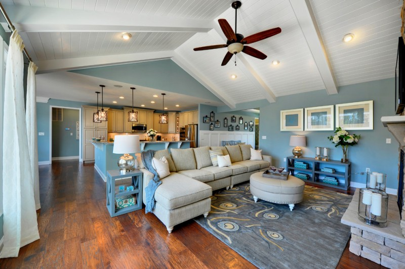 vaulted great room with kitchen and living room, blue walls, bue rug, blue shelves, blue side table, white table lamp, beige sofa, red ceiling fan