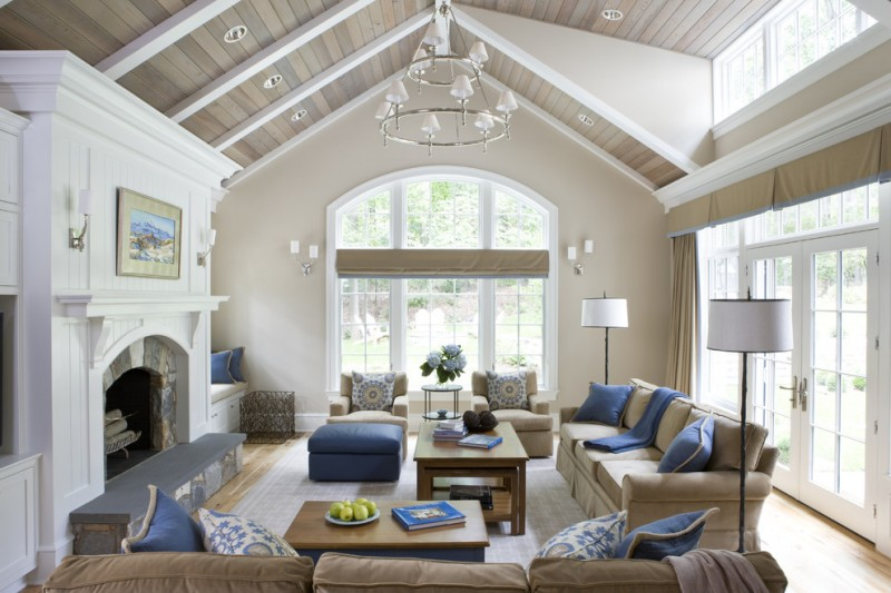 vaulted living room in white wall and ceiling, beige sofa, blue pillow, blue ottoman, white floor lamp, white chandelier