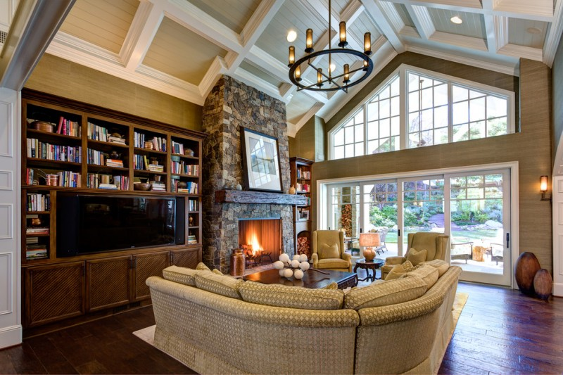 vaulted living room with brown ceiling and walls, brown sofa, dark wooden shelves, stone fire place, chandelier
