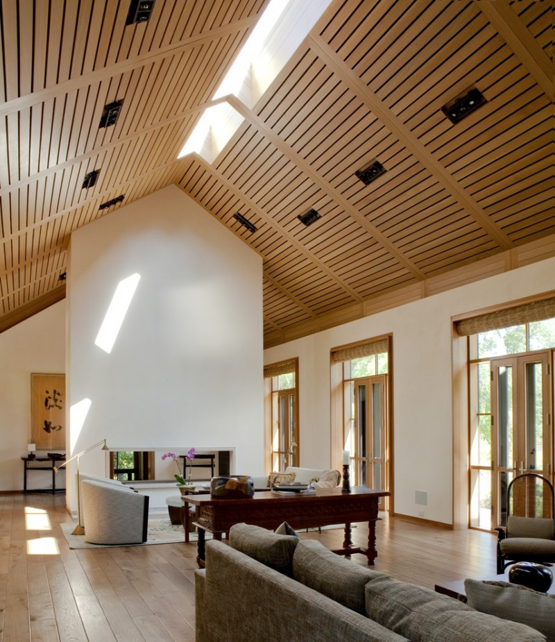 vaulted living room with wooden reeling ceiling, white wall, wood framed glass window, wood framed glass door, wooden flooring, grey sofa, side table, floor lamp