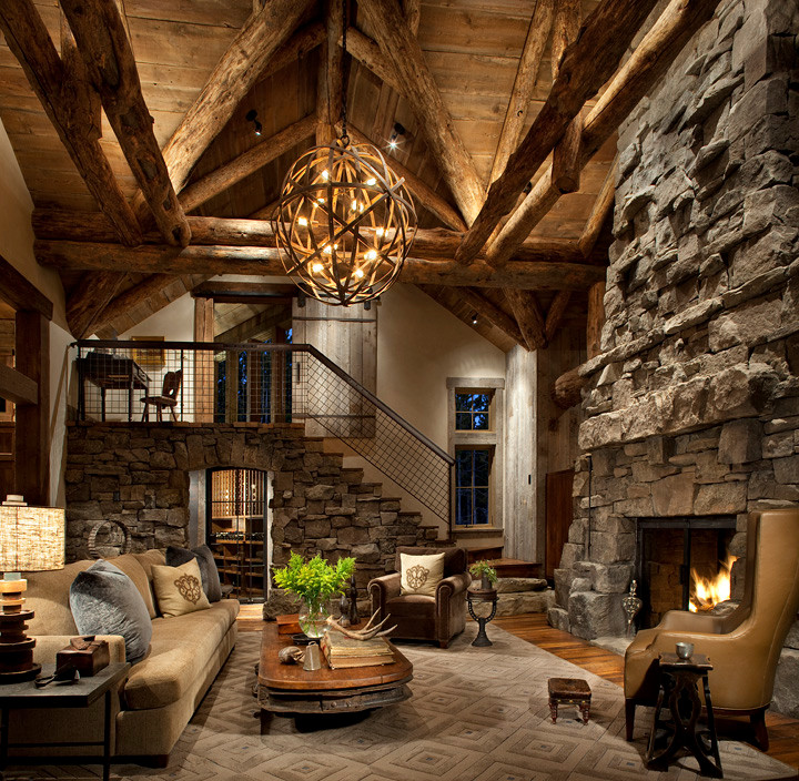 vaulted rustic living room with rough wooden beams, stone fireplace, wooden flooring, brown rug, wood table, brown sofa, brown couch