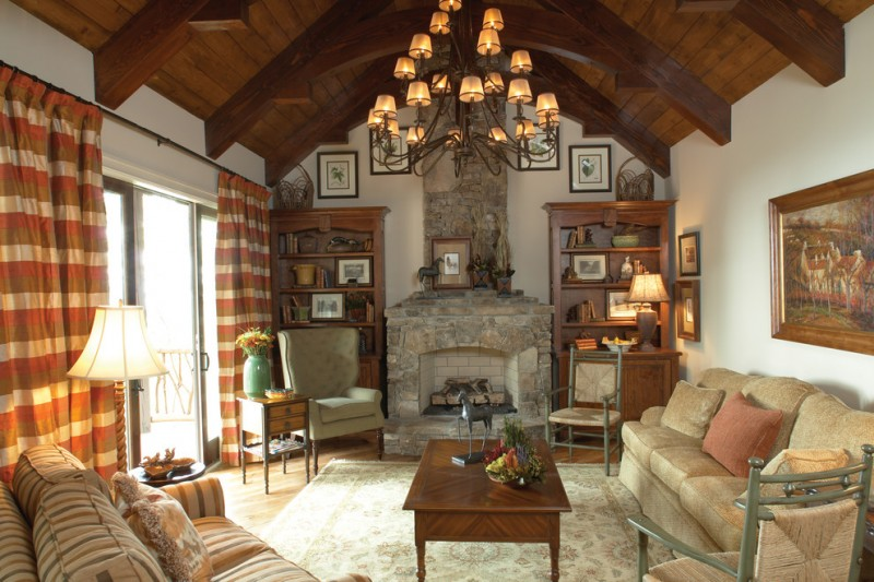 vaulted rustic living room with wooden beams in the ceiling, wooden flooring, white walls, stone fireplace, brown rug, brown sofa, wood table, chendelier