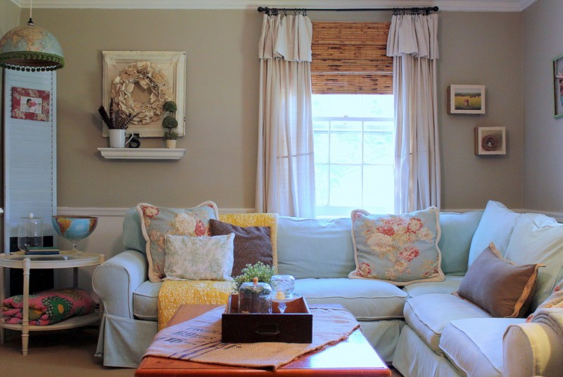 vintage style living room shabby white half curtain with black metal rods L shape white sofa with pillows side table with lower shelf wooden center table