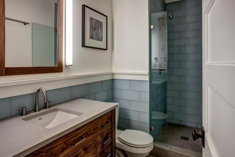 walk in bathroom design with blue glass tiles walls and dark beige tiles floors white countertop and wooden cabinets undermount sink glass panel door