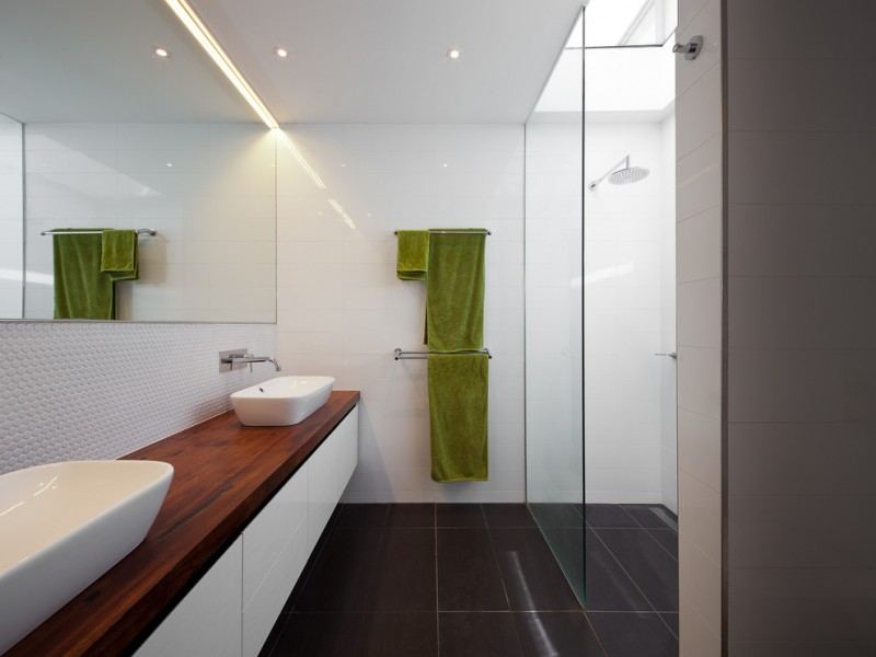 walk in bathroom with black tiles floors textured white tiles backsplash full length vanity with wooden top and white double sinks frameless mirror wall mount chrome panel for hanging towels