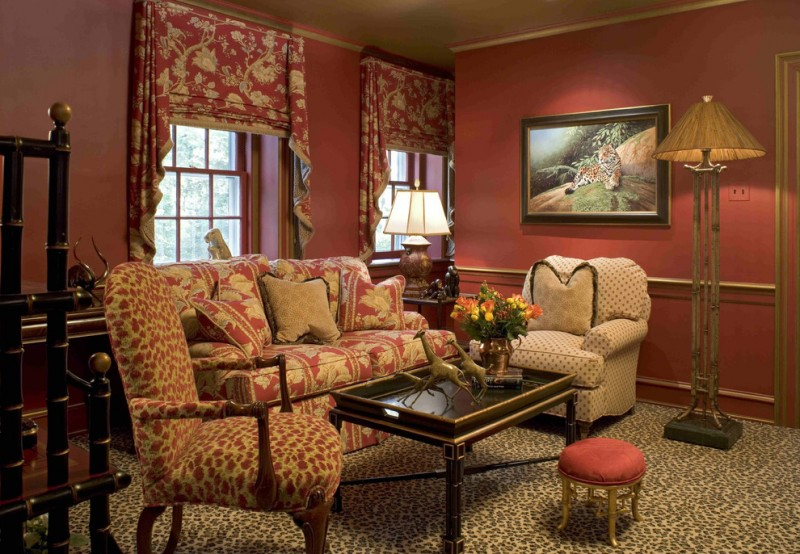 warm living room with animal pattern rug, animal pattern couch, bamboo copper legs floor lamp, red ottoman, giraffe miniature, orangutan miniature, tiger painting, floral sofa, floral curtain