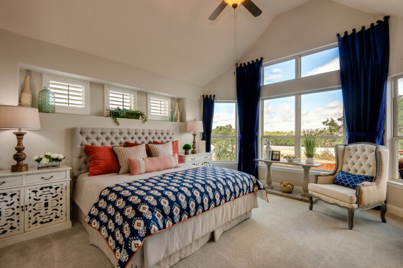 white bed linen with navy blue blanket with beautiful motifs and colorful pillows bed set with headboard luxurious white bedside tables decorative window with white shutters on top