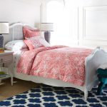 White Bed Sheet With Little Bit Coral Accent Coral Toned Comforter With White Motifs White Navy Blue Rug White Bed With Traditional Headboard White Bedside Tables With Table Lamps Textured Floors