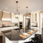 White Cabinet Black Granite Countertop Cream Wall Glass Ceiling Lights Brick Wall Dark Hardwood Floor