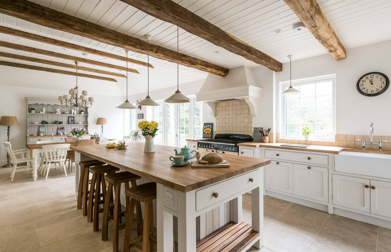 white cabinet pendant lights brick backsplash wooden beams wooden stools wooden topped table open shelves