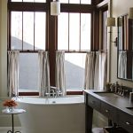 White Half Curtains Window For Bathroom In Lake House White Free Standing Tub Dark Finishing Wooden Vanity Undermount Sink In Square Shape White Ceramic Floors Black Framed Mirror