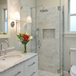 White Marble Walk In Shower With Frameless Glass Panels White Marble Top Vanity With White Finished Cabinets White Toilet Recessed Shelf Under Mount Sink