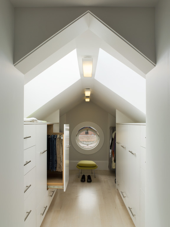 white melanine walk in closet organizer in slanted roof dressing room rounded glass window with white frame green chair a pair of skylight