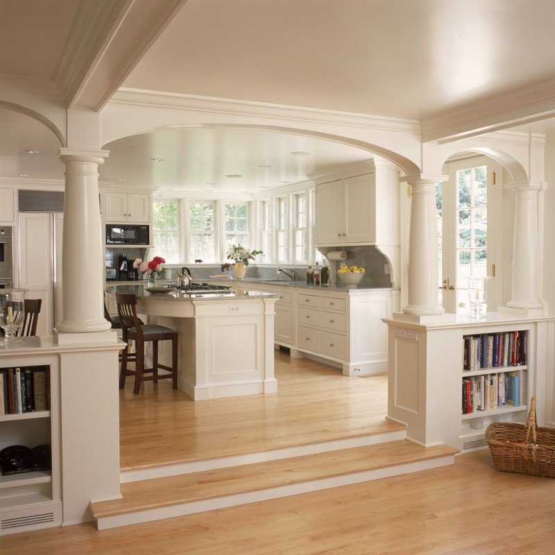 white open kitchen with wooden floor, white cabinet, white walls, window, ceiling, white counter top, arch wall, stairs to the living room