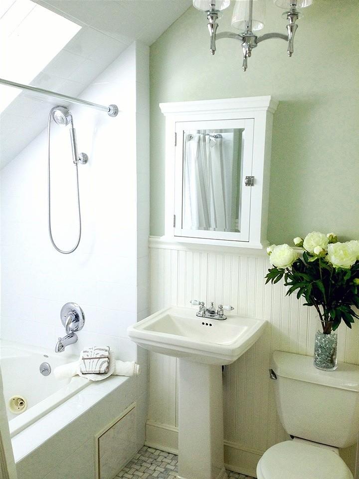 white small master bathroom with white bahttube, white cabinet mirror, white sink, white toilet, white chandelier