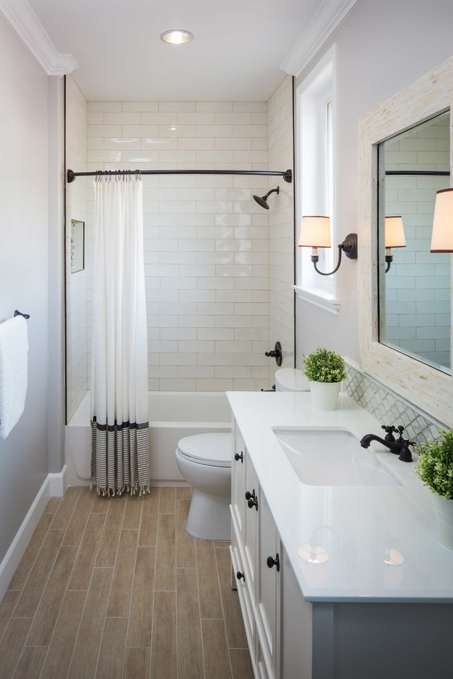 white subway tiles for shower walls drop in tub in white white shower curtain white toilet white vanity and cabinets wooden tiles floors black finish fixtures frameless mirror
