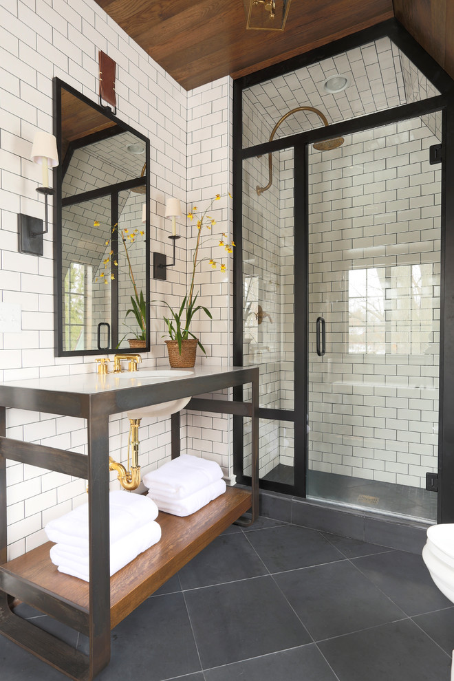 white subway tiles walls and ceiling in shower space glass panels and door with black frames simple vanity with white countertop and undermount sink mirror with black frames black ceramic
