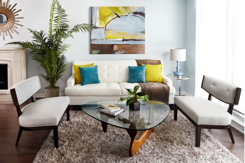 white upholstered sofa with green and yellow pillows, white bench with cushion, glass coffee table