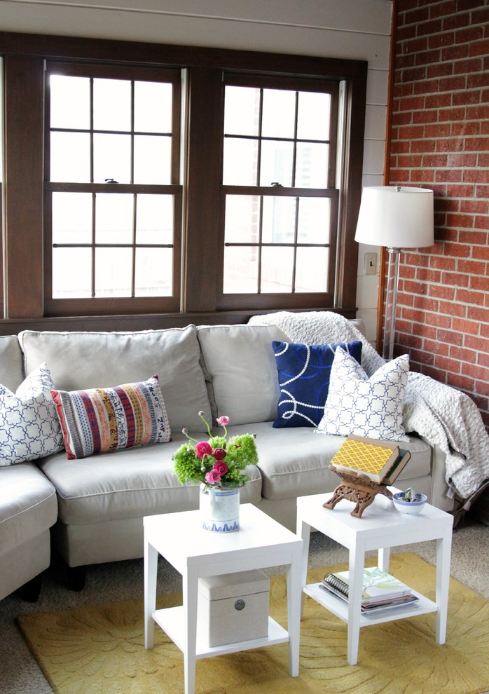 white upholstered sofa with white cushion, colorful pillows, and two white wooden coffee table