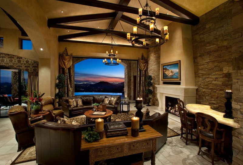 wood beams ceiling lamps decorated arch window dark sofa wooden sofa table brick wall rounded wooden coffee table