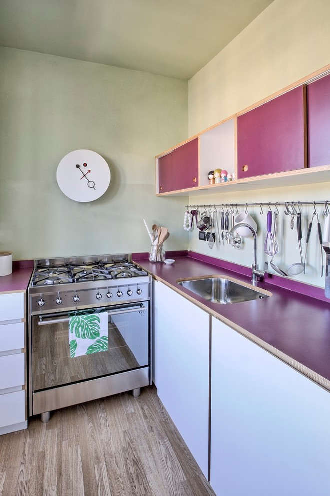 L shape kitchen stainless steel appliances purple countertop white lower cabinets purple upper cabinets metal hang section for cooking tools stainless steel sink wooden floors without finish